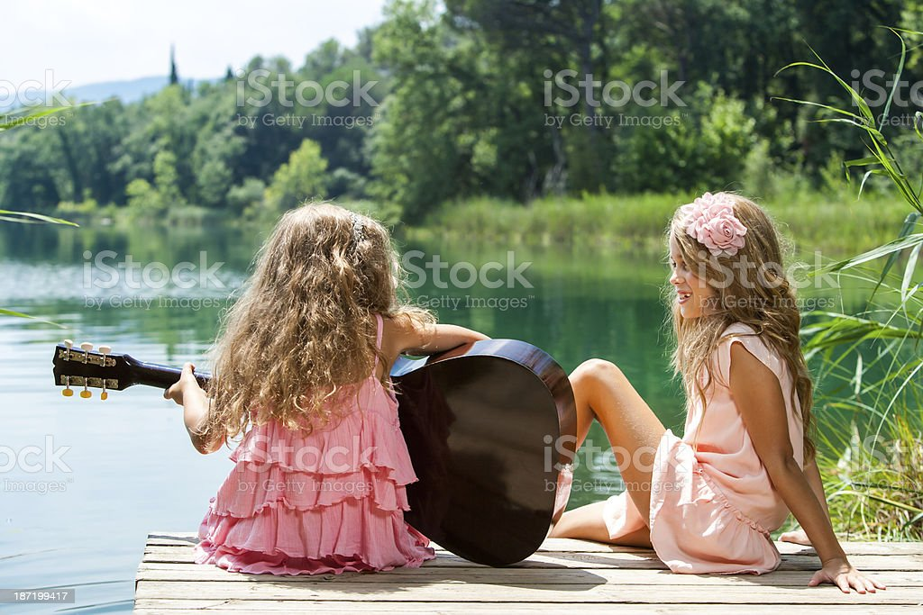 Young girls singing together with guitar. royalty-free stock photo