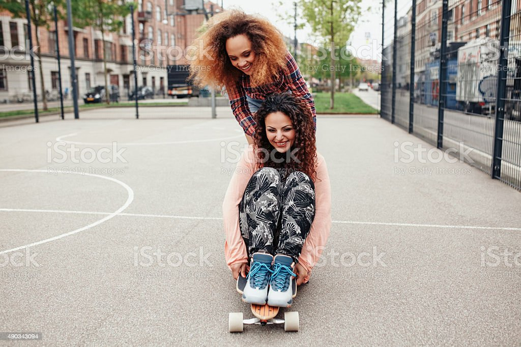 Young girls skating in basketball court stock photo