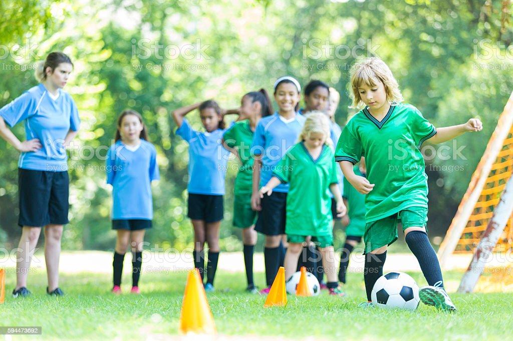 Young girls soccer team runs through drills stock photo