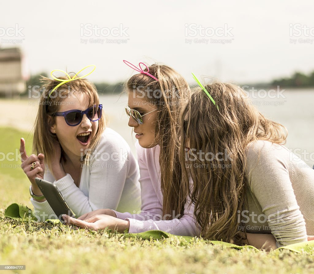 Young girls using tablet and cell phone royalty-free stock photo