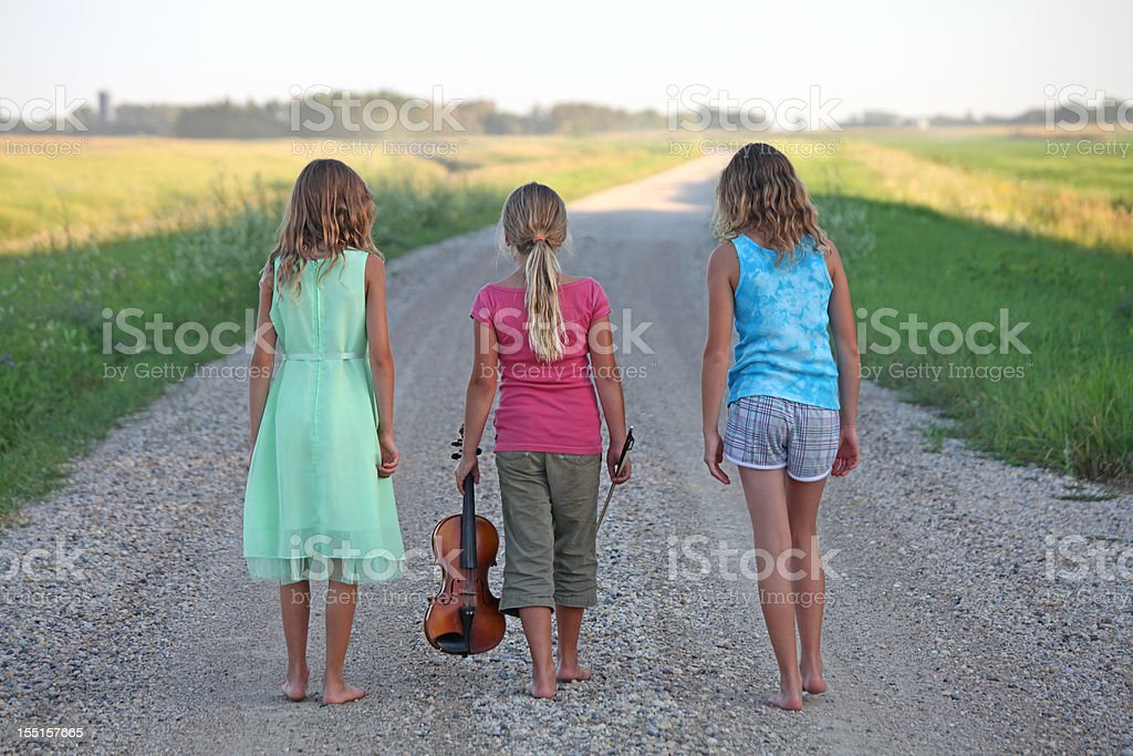 Young Girls Walking Down Rural Gravel Road in Summer royalty-free stock photo