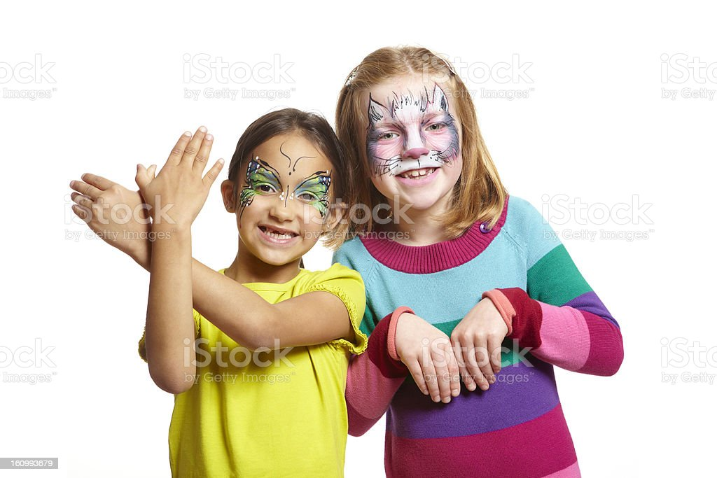 Young girls with face painting of cat and butterfly stock photo