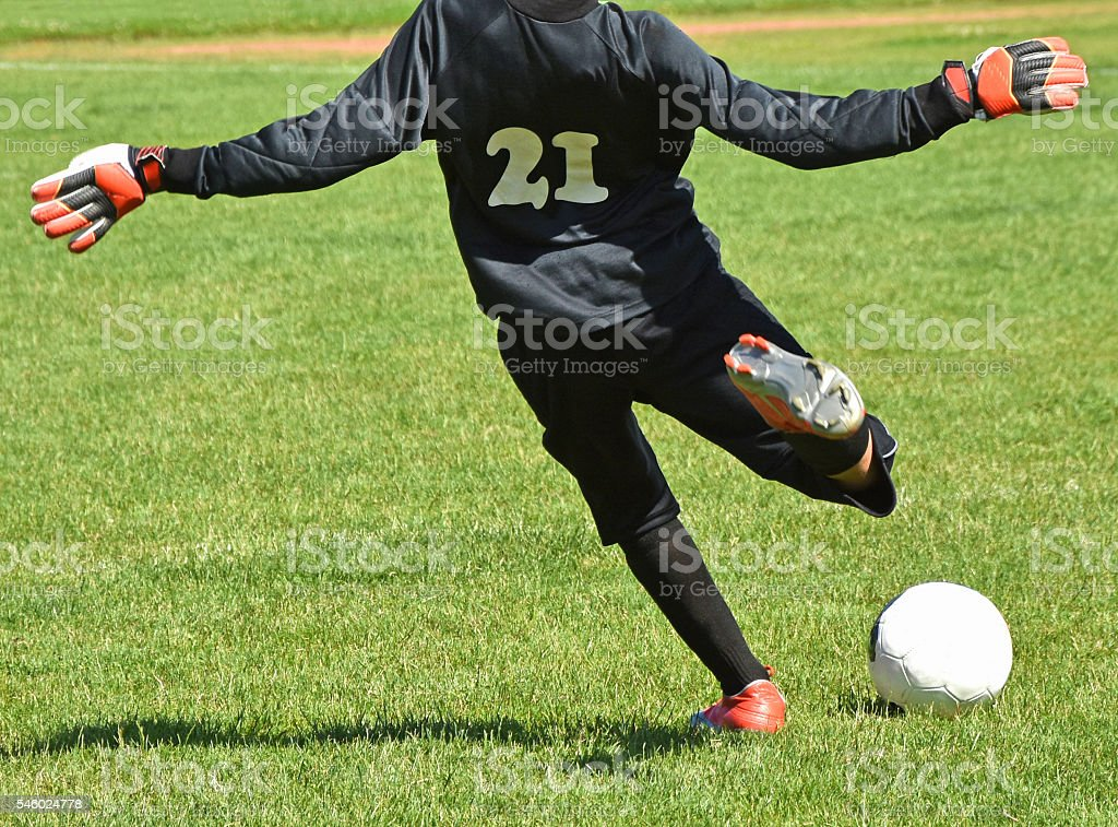 Young goalkeeper kicks off the ball stock photo