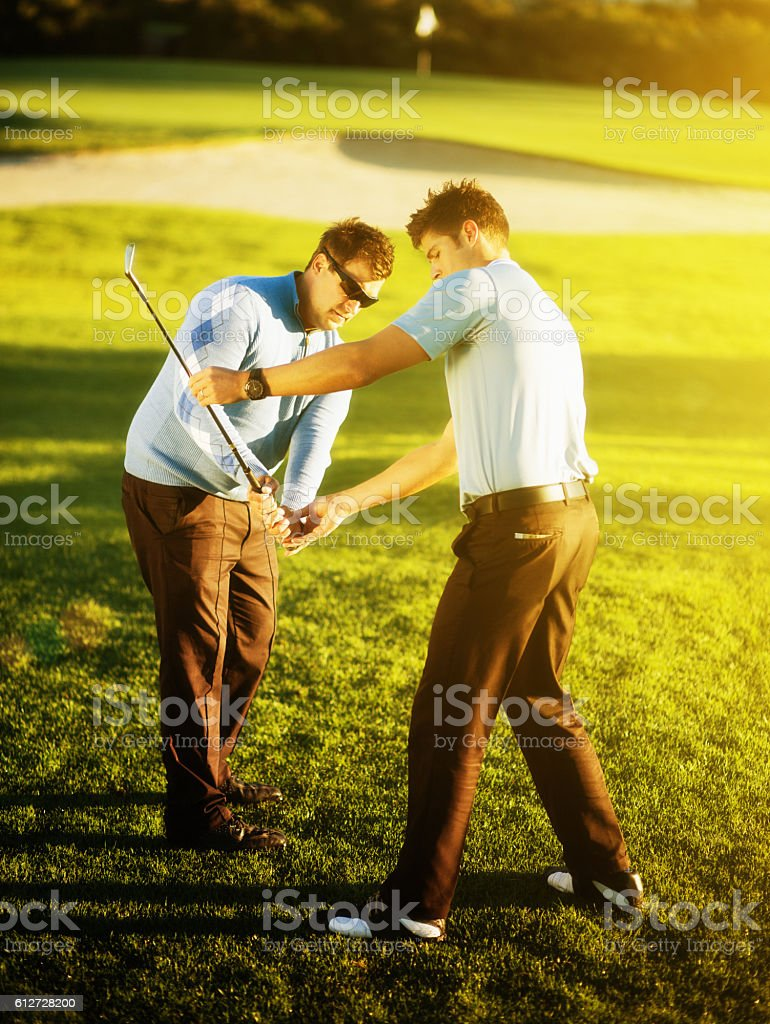 Young golf coach correcting golfer's swing on sunlit course stock photo