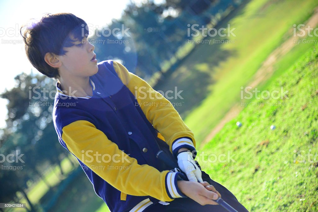 Young golf player in red in open air park stock photo