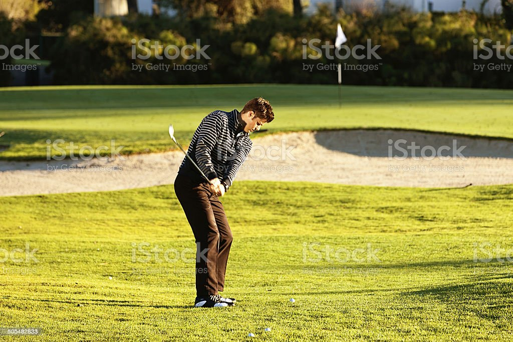 Young  golfer aiming to hit over sandtrap to reach green royalty-free stock photo
