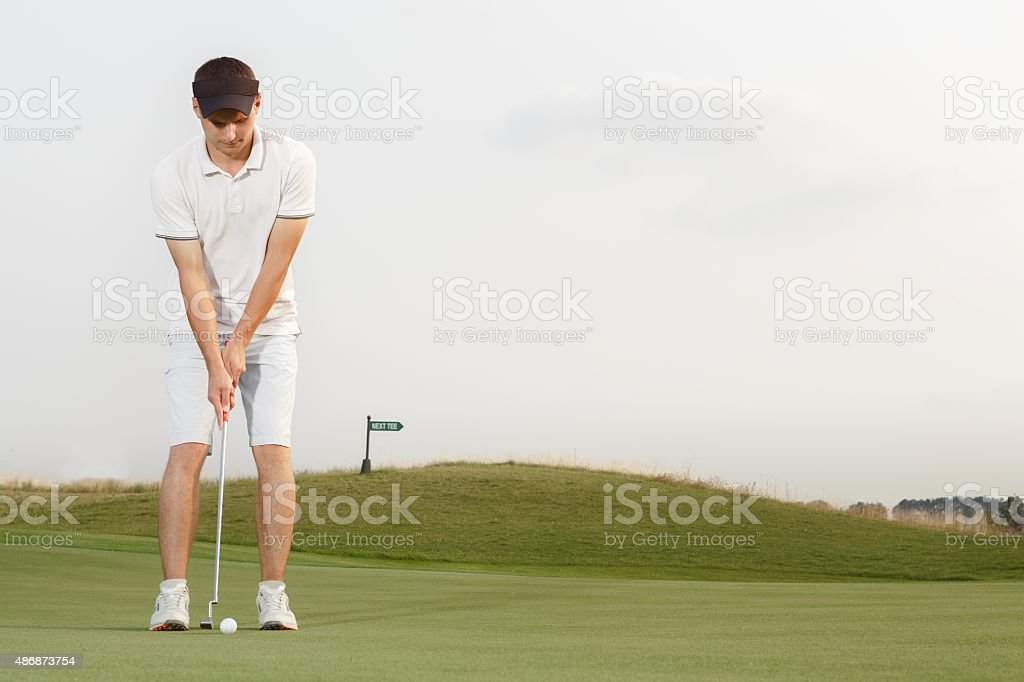 Young golfer getting ready to hit the ball stock photo