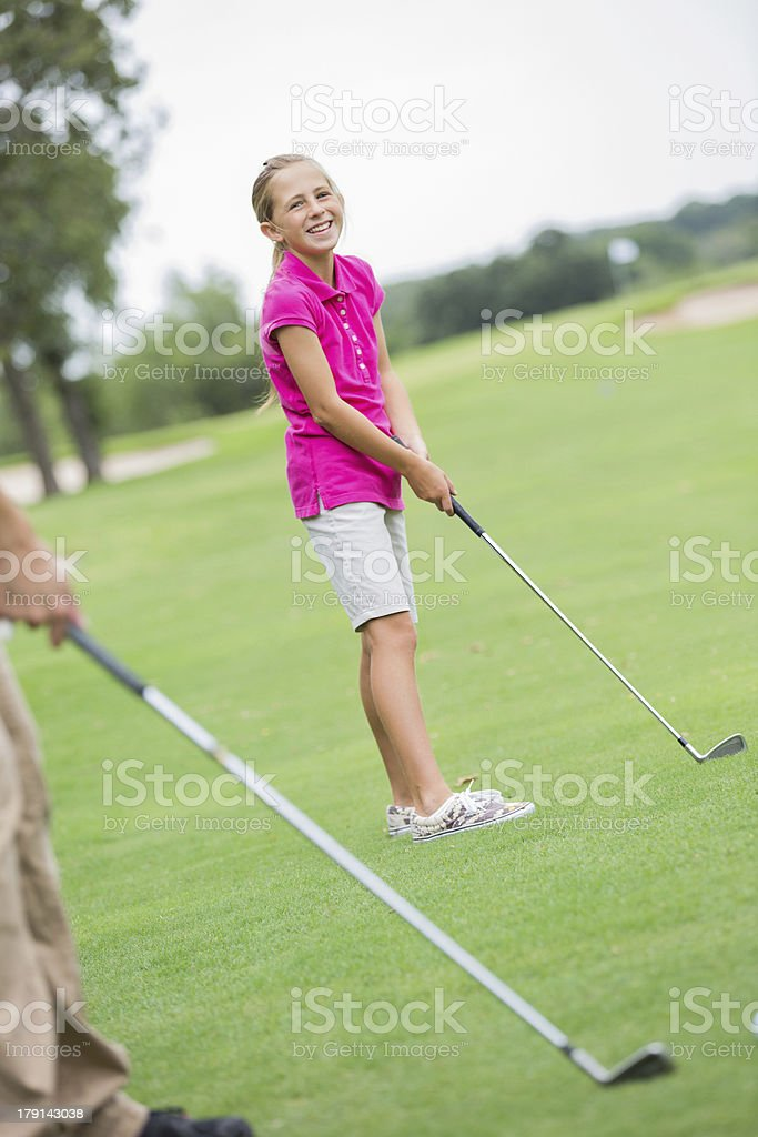 Young golfer girl playing golf with family on course royalty-free stock photo
