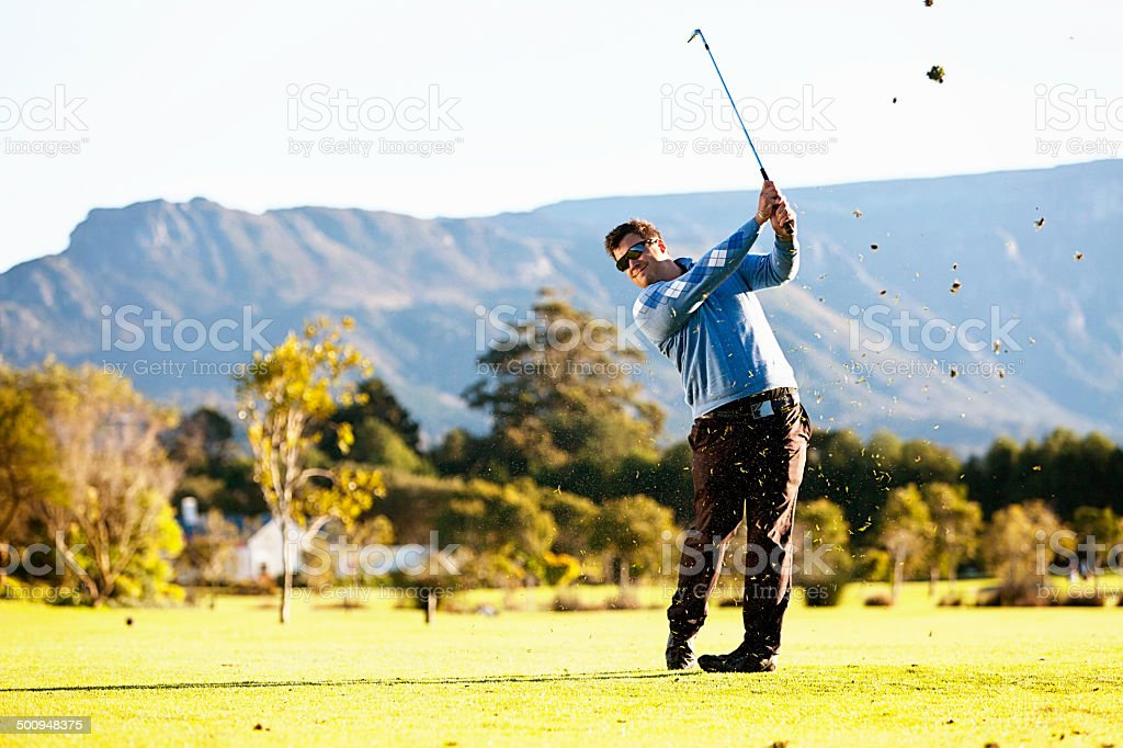 Young golfer hits ball so clods of earth fly up stock photo