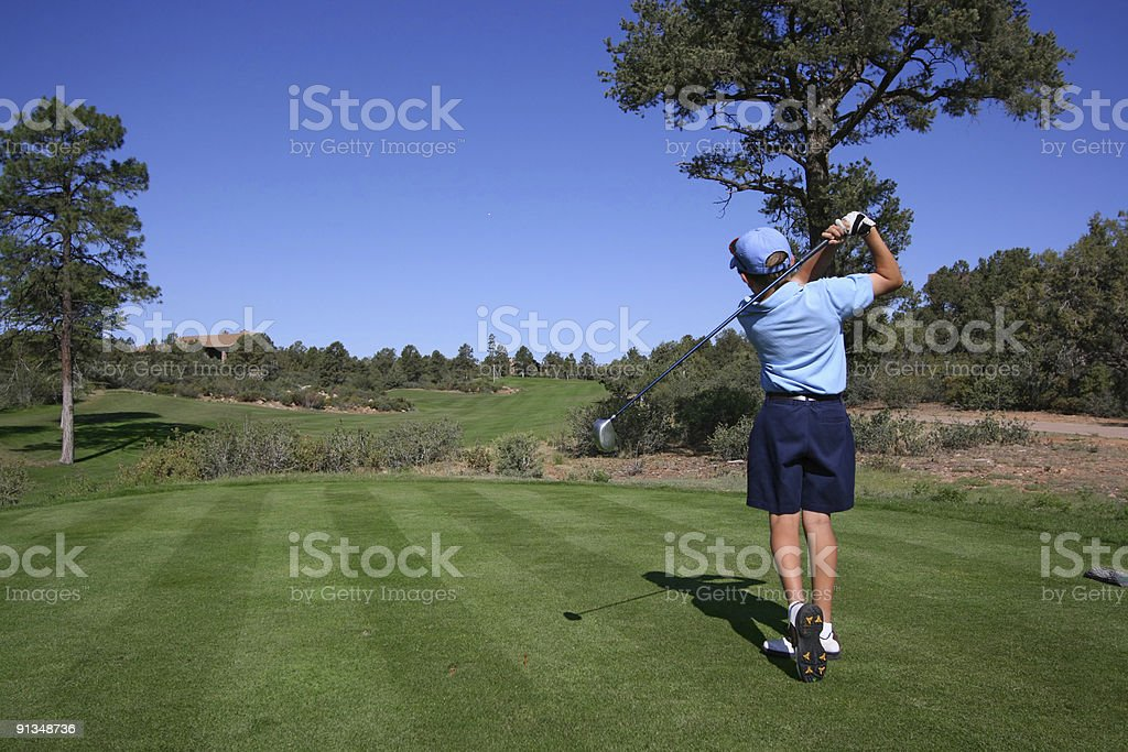 Young golfer hitting a nice tee shot royalty-free stock photo