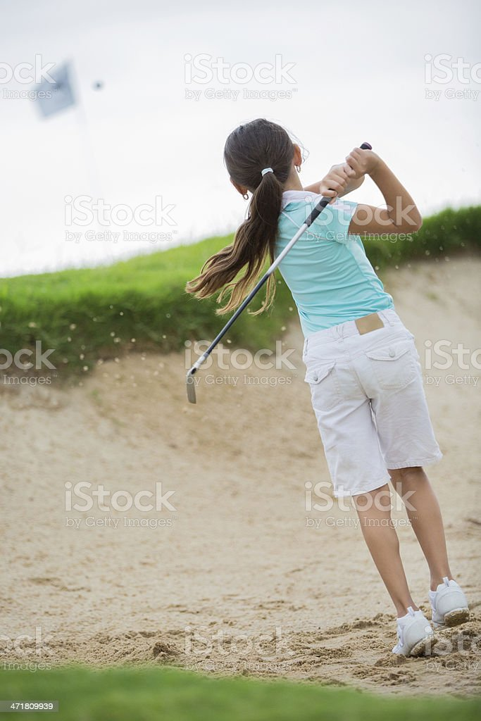 Young golfer hitting golf ball out of sand trap stock photo