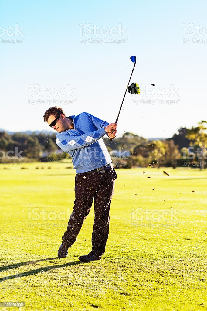 Young golfer muffs a shot, throwing divots into the air stock photo