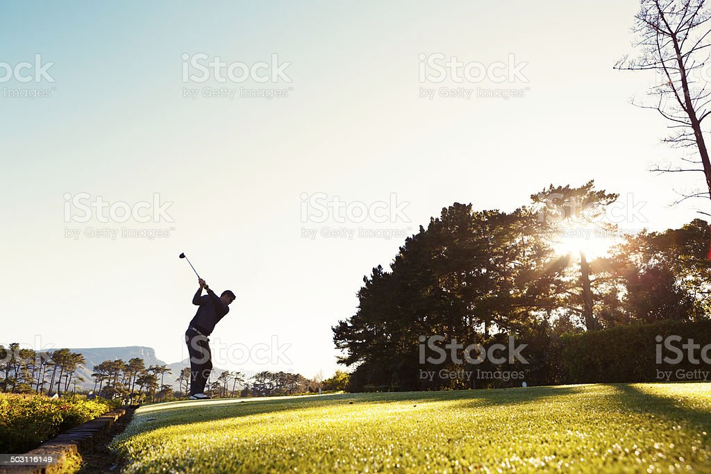 Young golfer, silhouetted against morning sun, tees off stock photo