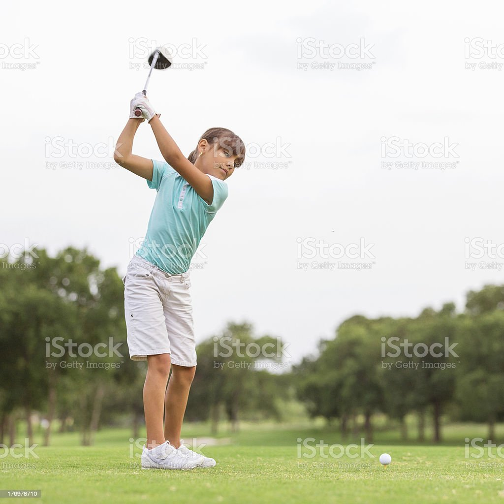 Young golfer teeing off on beautiful golf course royalty-free stock photo