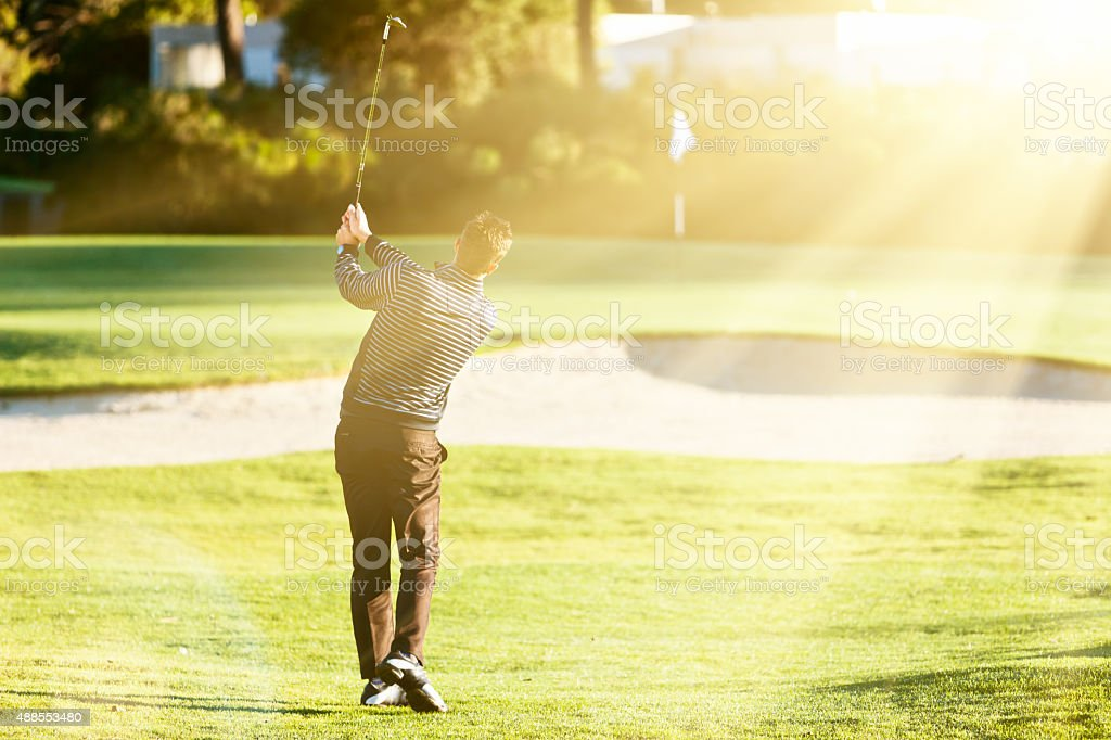 Young golfer trying to avoid sandtrap with lofted shot stock photo