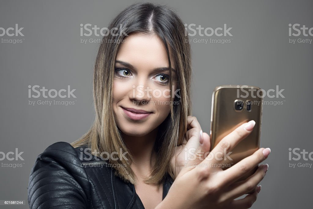 Young gorgeous green eyed beauty taking selfie stock photo