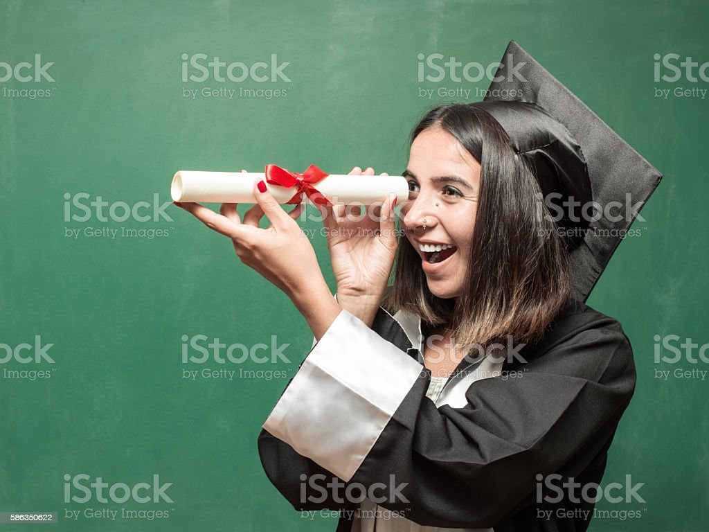 Young Graduate Woman Looking Through Her Diploma As A Binocular stock photo