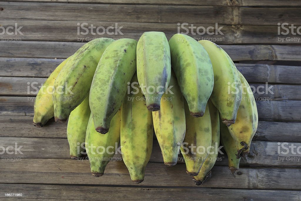 Young green banana on wooden table royalty-free stock photo