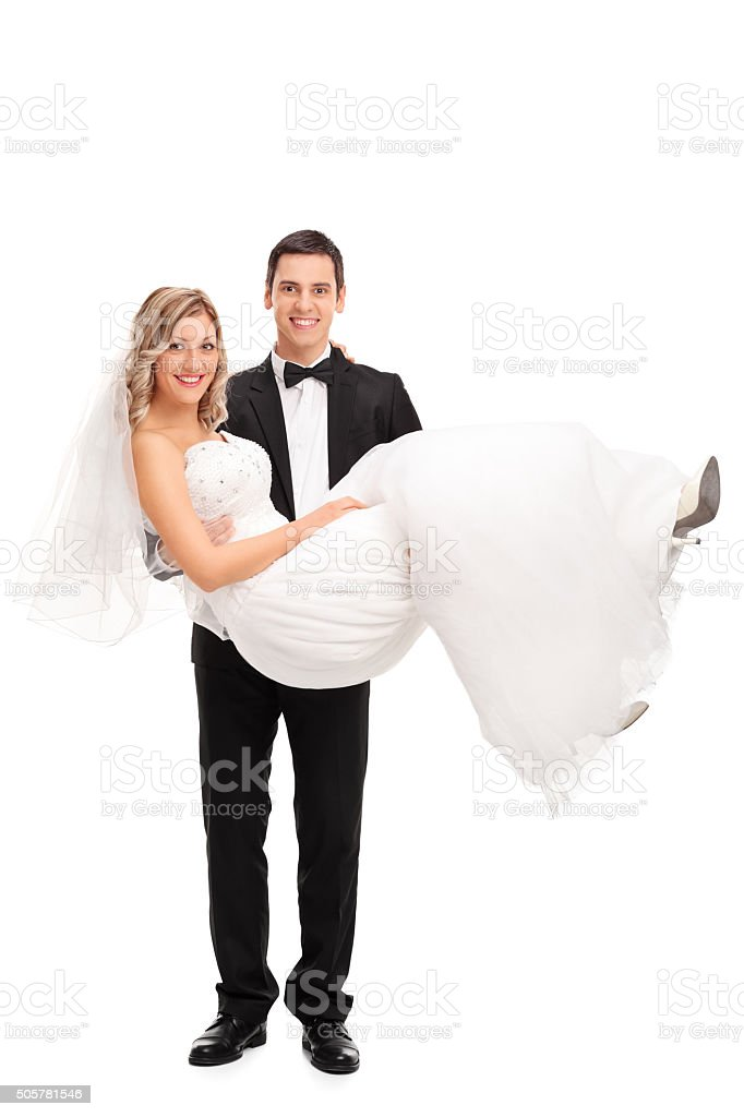 Young groom carrying a bride in his hands stock photo