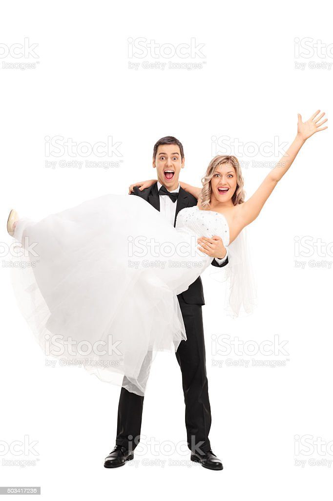 Young groom lifting his bride in his hands stock photo