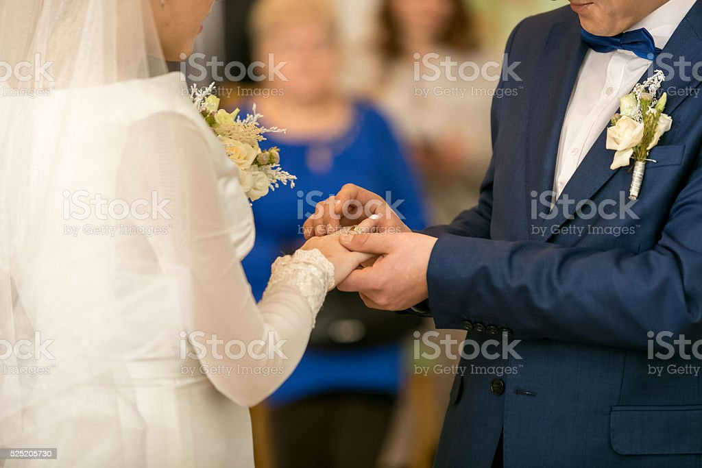 Young groom putting wedding ring on bride's finger stock photo