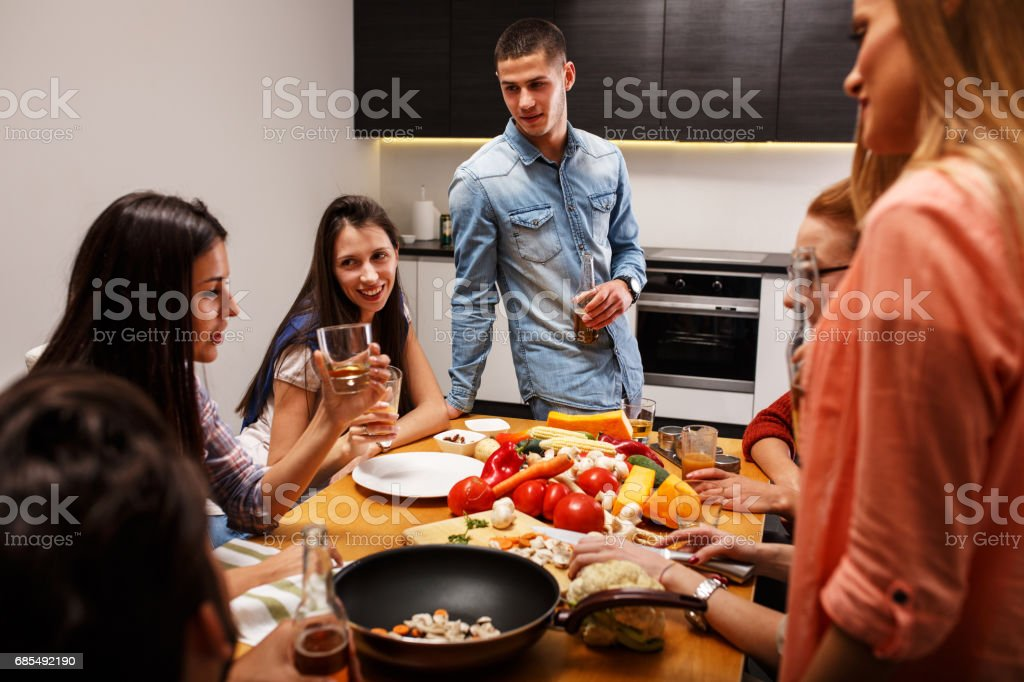Young group of friends in kitchen preparing together vegetarian meal stock photo