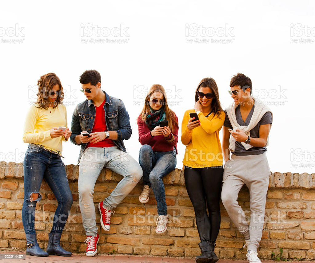 Young group of friends with smart phones stock photo