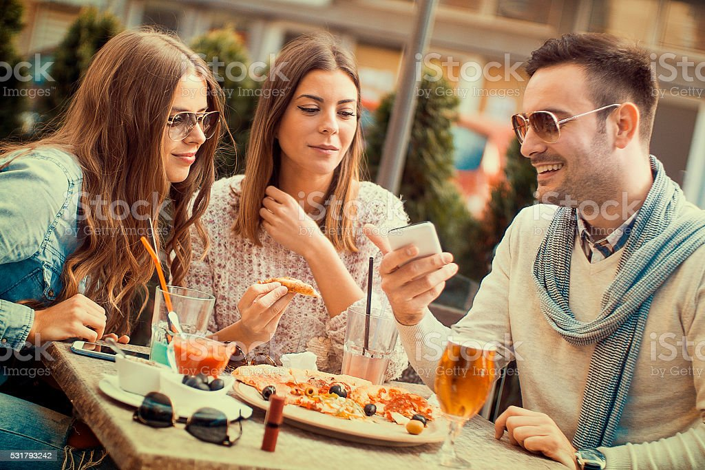Young group of laughing people eating pizza and having fun stock photo