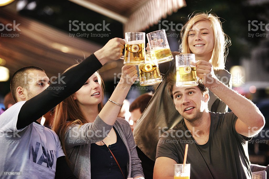 Young group of people having fun on a sidewalk bar stock photo
