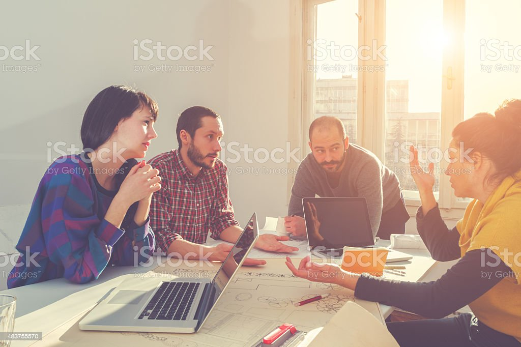 Young group of people/architects discussing business plans stock photo