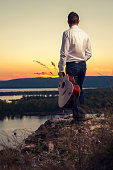 Young guitarist standing on the river bank