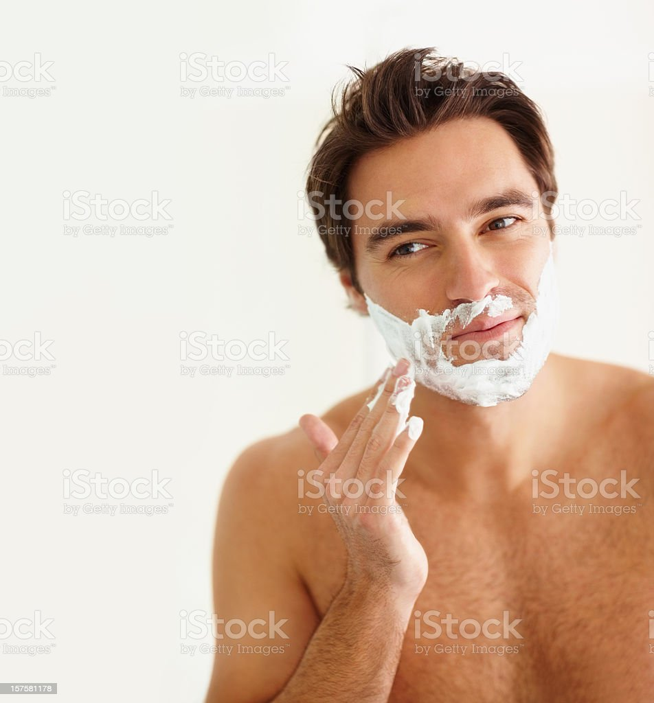 Young guy applying cream to his face for a shave royalty-free stock photo