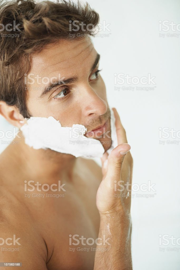 Young guy applying shaving cream on face royalty-free stock photo
