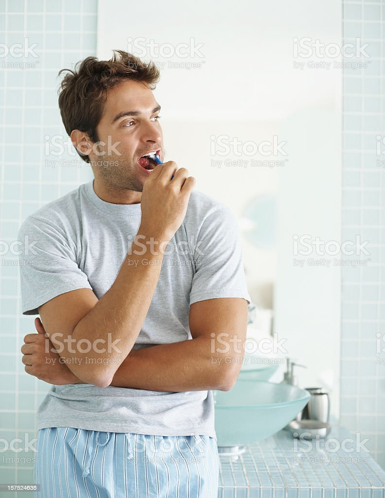 Young guy brushing his teeth in  the bathroom stock photo