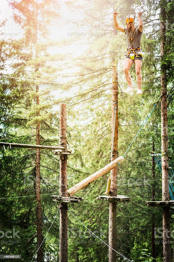 Young guy climbing  rope in climbing forest nature bakgrund stock photo