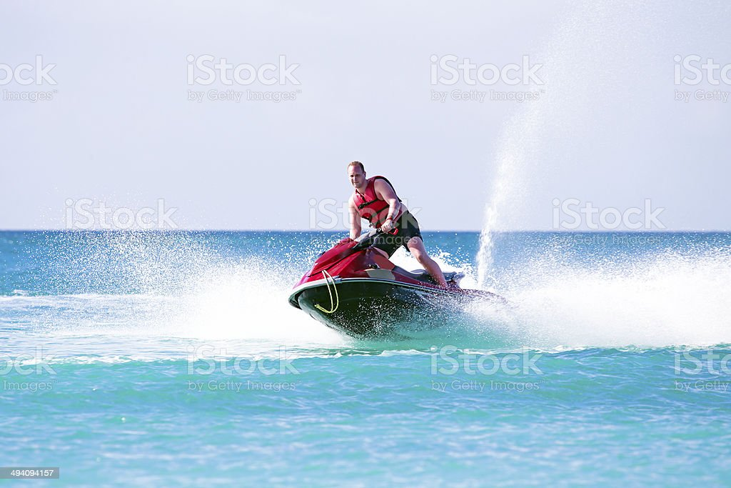 Young guy cruising on a jet ski stock photo