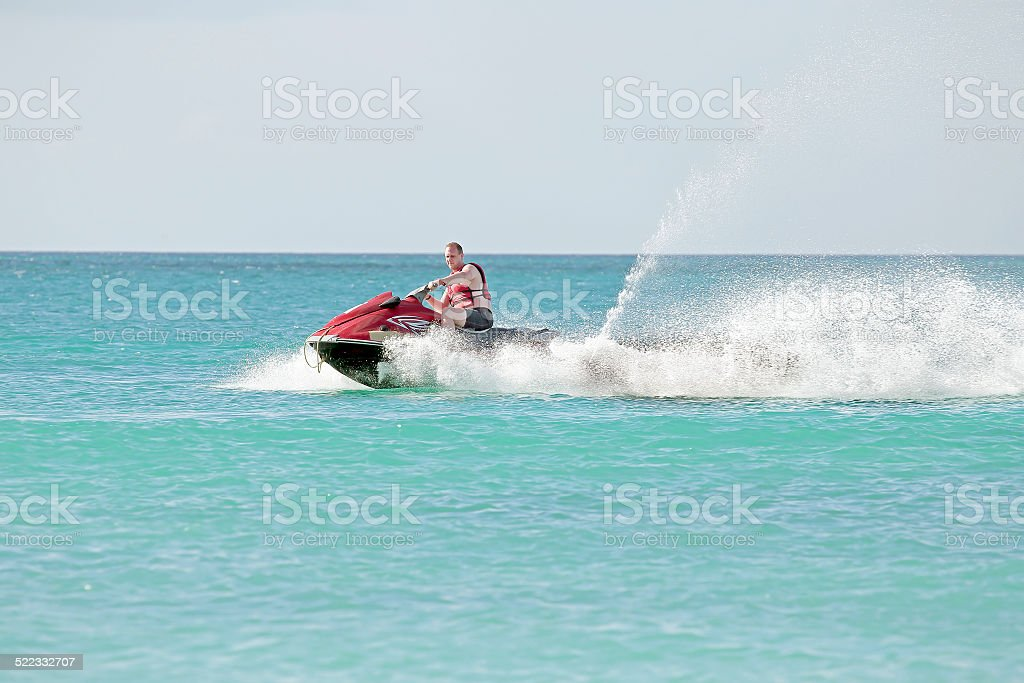 Young guy cruising the caribbean sea on a jet ski stock photo