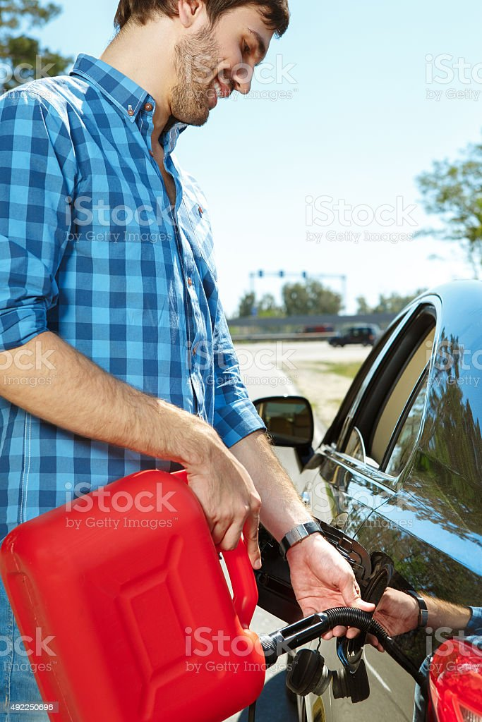 Young guy filling his car stock photo