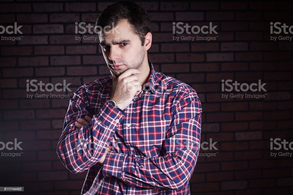 young guy in a plaid shirt frowns stock photo