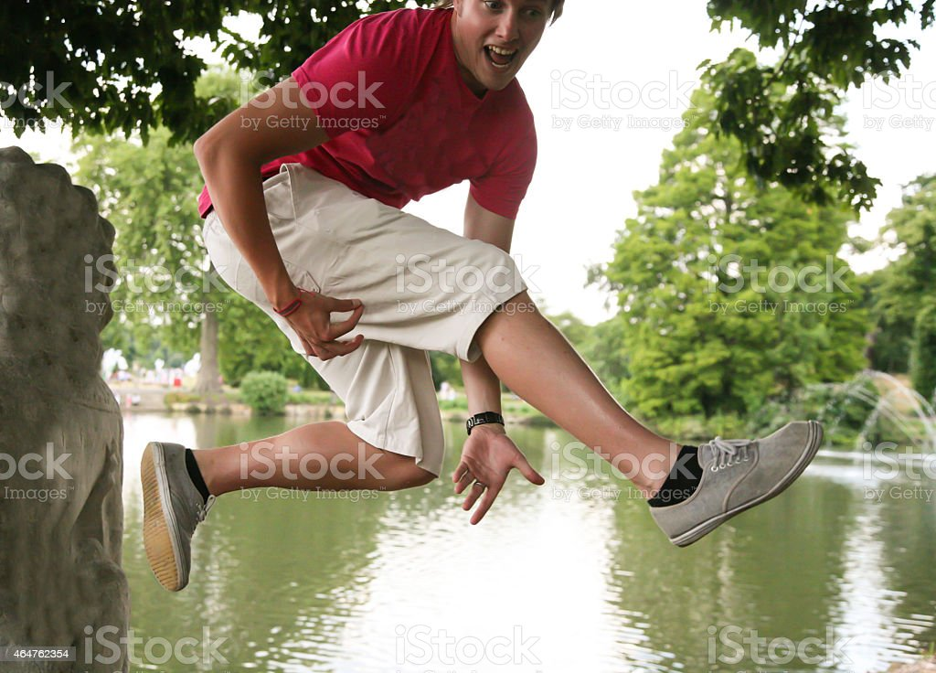 Young guy leaping to the air and playing air guitar stock photo