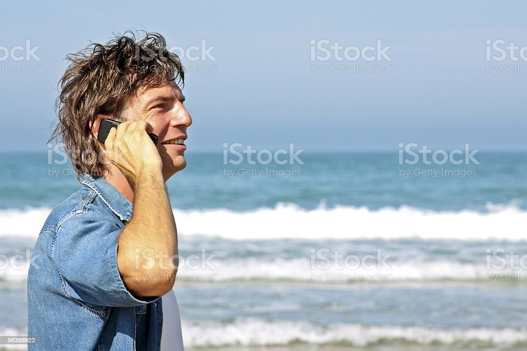 Young guy making a phonecall on the beach royalty-free stock photo