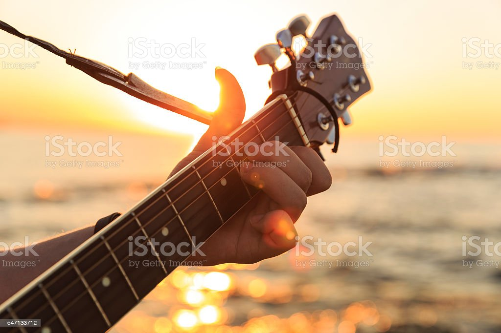 Young guy playing a guitar at sunset(Soft Focus) stock photo
