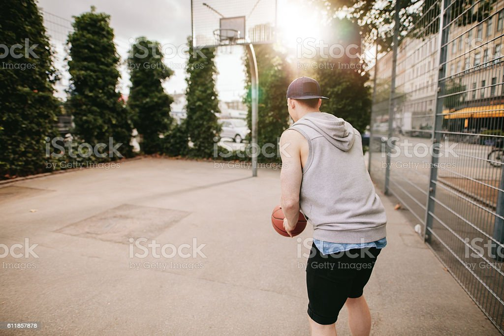 Young guy playing basketball on outdoor court stock photo