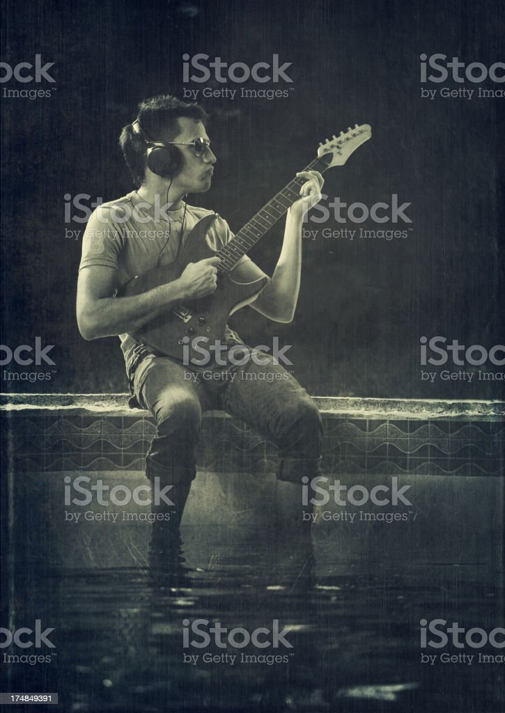 young guy playing electric guitar by the pool royalty-free stock photo