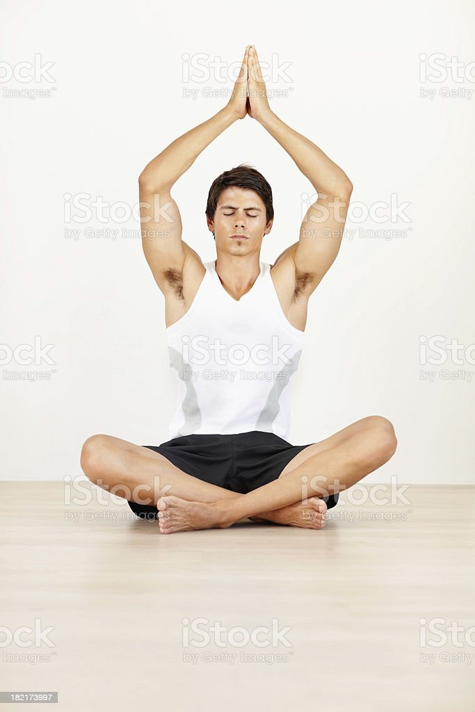 Young guy practicing yoga with hands joined above head royalty-free stock photo