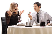 Young guy proposing to his girlfriend at a restaurant table
