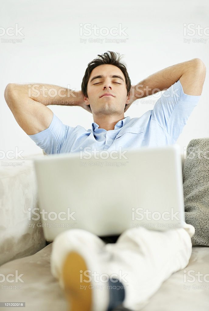 Young guy relaxing on couch with a laptop royalty-free stock photo