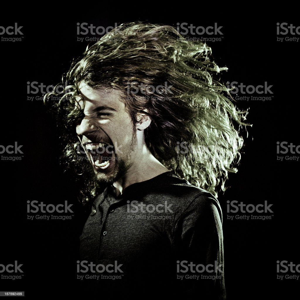 young guy screaming in the dark stock photo