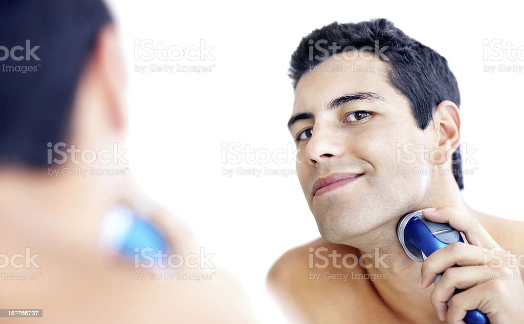 Young guy shaving his beard off with an electric shaver royalty-free stock photo