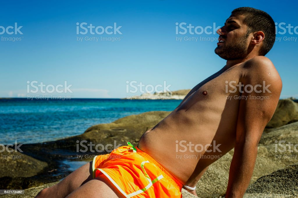 Young guy sitting on the rock and exposes to sun stock photo